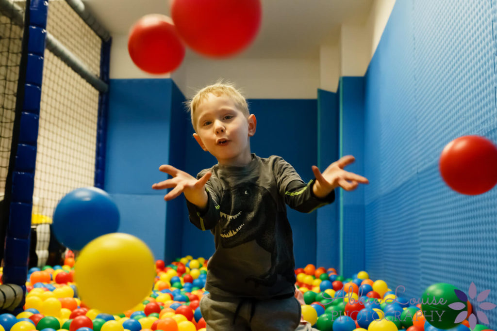 birthday boy throwing balls in ball pit at camera at celebration