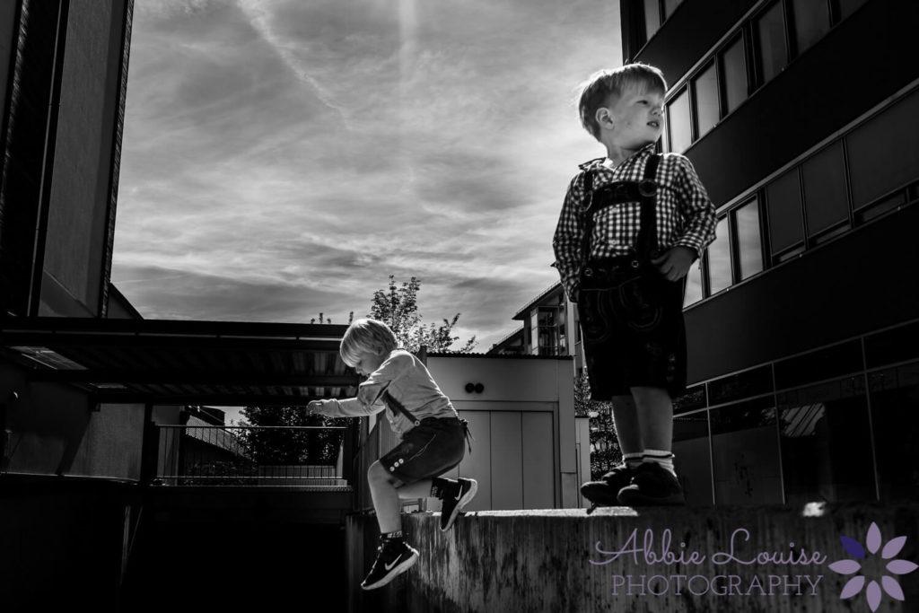 two boys on a wall in lederhosen