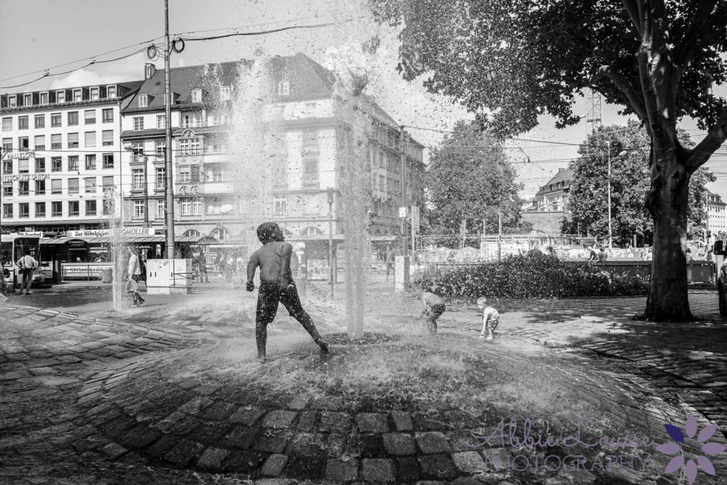 Munich child playing in public fountain